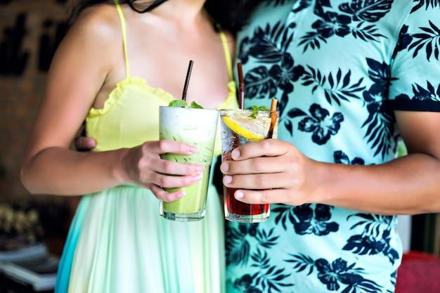 Joven pareja feliz bebiendo sabrosos cócteles dulces en el bar tropical, sonriendo y divirtiéndose, ropa brillante y emociones positivas.