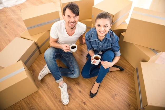 La joven pareja feliz bebiendo té y café.