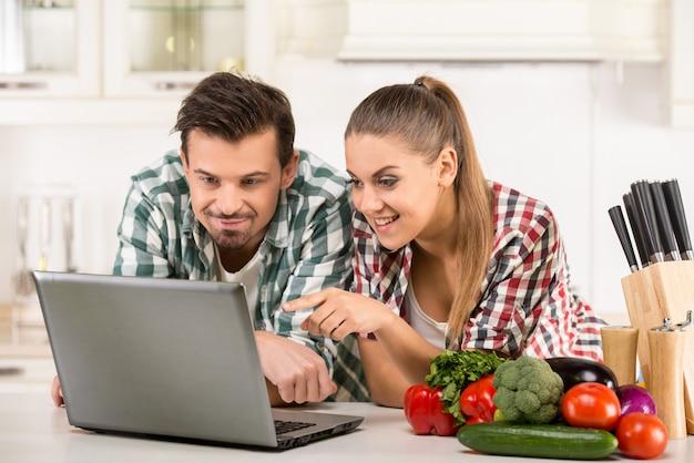 Joven pareja feliz está buscando receta.