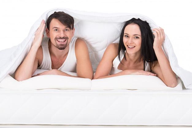 Joven pareja feliz en una cama