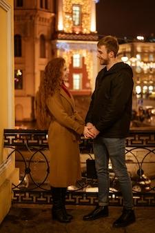 Joven pareja feliz caminando por la ciudad en la noche