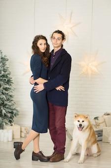 Joven pareja feliz caricias y besos mientras está sentado en un banco junto a un perro