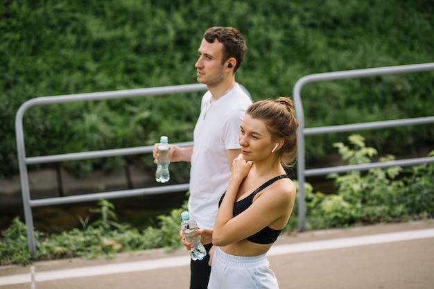 Joven pareja feliz corriendo en el parque de la ciudad con una botella de agua en las manos, deportes conjuntos, alegría, estilo de vida saludable del deporte de la ciudad, fitness juntos en la noche de verano