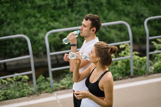 Joven pareja feliz corriendo en el parque de la ciudad con una botella de agua en las manos, deportes conjuntos, alegría, estilo de vida saludable del deporte de la ciudad, fitness juntos en las noches de verano, corredores, agua potable, sed