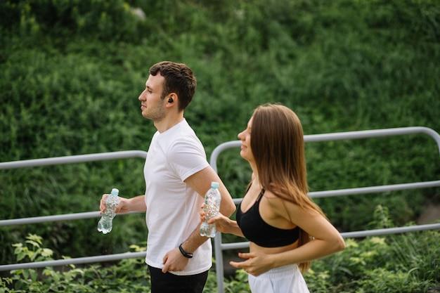 Joven pareja feliz corriendo en el parque de la ciudad con una botella de agua en las manos, deportes conjuntos, alegría, estilo de vida saludable del deporte de la ciudad, fitness