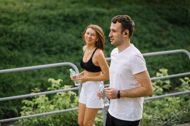 Joven pareja feliz corriendo en el parque de la ciudad con una botella de agua en las manos, deportes conjuntos, alegría, estilo de vida saludable del deporte de la ciudad