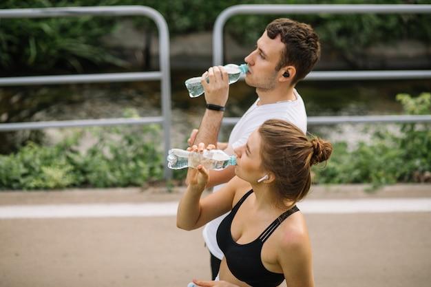 Joven pareja feliz corriendo en el parque de la ciudad con una botella de agua de plástico en las manos, deportes conjuntos, alegría, estilo de vida saludable del deporte de la ciudad, fitness juntos, corredores, agua potable, sed