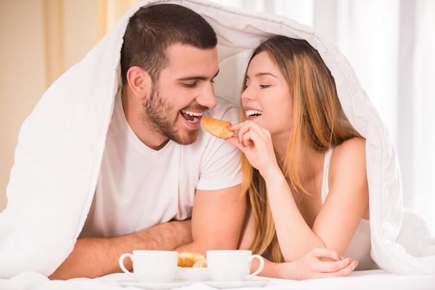 Joven pareja feliz desayunando en su dormitorio.