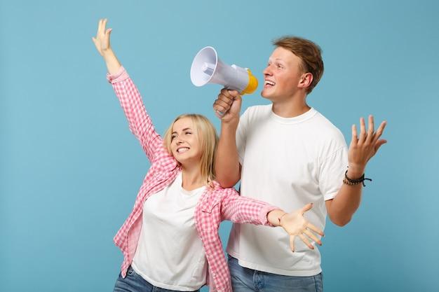 Joven pareja feliz dos amigos chico y mujer en camisetas blancas rosa vacías posando