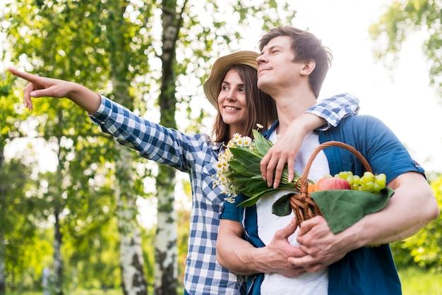 Joven pareja feliz elegir lugar de picnic en la naturaleza