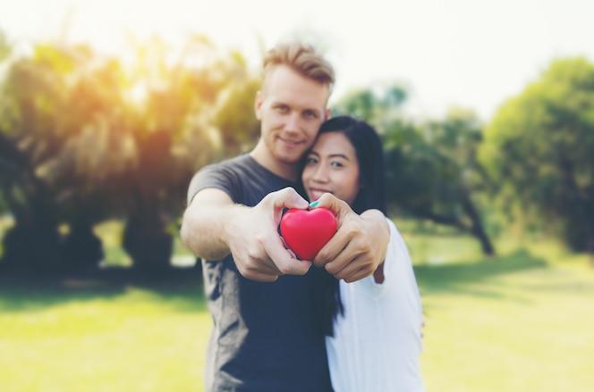 Joven pareja feliz en el amor con corazón rojo día de san valentín en el parque