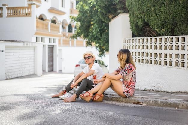Joven pareja feliz enamorada camina por las callejuelas de españa, bebe champán, ríe. vacatio