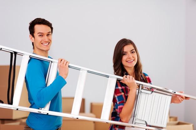 Joven pareja feliz con una escalera durante la mudanza a casa nueva