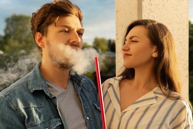 Joven pareja feliz fumar narguile en un balcón