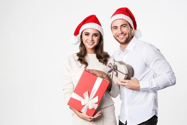 Joven pareja feliz con gorro de papá noel con cajas de regalo aisladas