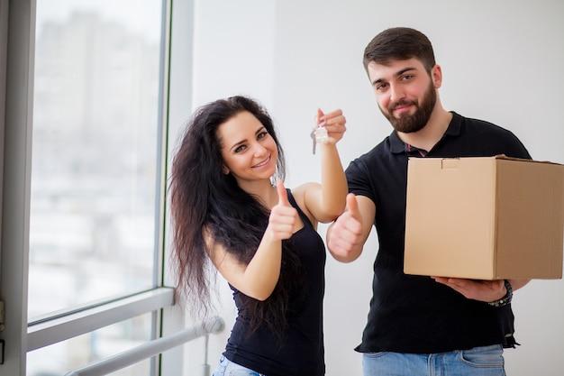Joven pareja feliz hablando mientras está de pie en su nueva casa