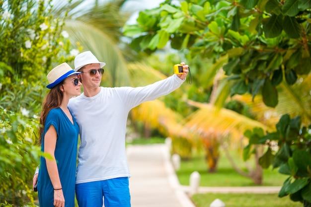 Joven pareja feliz haciendo selfie con teléfono móvil en vacaciones tropicales