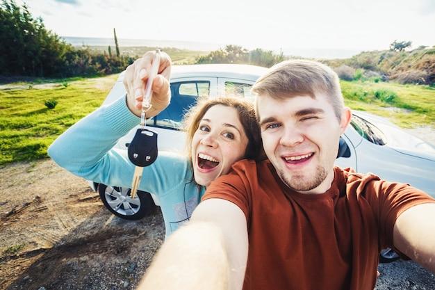 Joven pareja feliz con llaves para coche nuevo al aire libre.