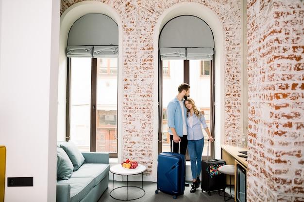 Joven pareja feliz llegó a la habitación de hotel en luna de miel o viaje de negocios.