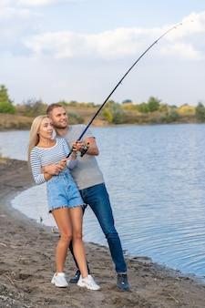 Joven pareja feliz pescando junto al lago