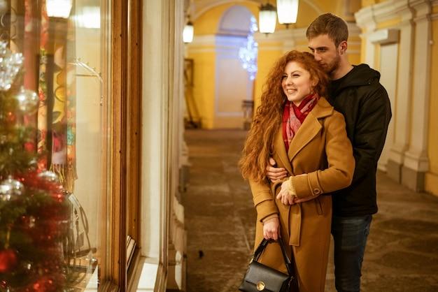 Una joven pareja feliz de pie en la calle mirando las ventanas en la noche