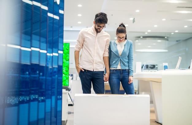 Joven pareja feliz de pie detrás de una gran caja de dibujos animados en el suelo y mirando hacia abajo después de comprar un nuevo producto electrónico en la tienda de tecnología.