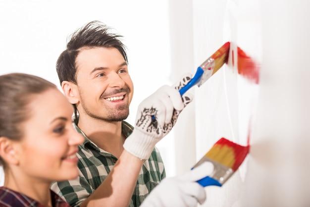 Joven pareja feliz está pintando un corazón en la pared.