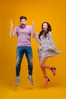 Joven pareja feliz saltando y sonriendo
