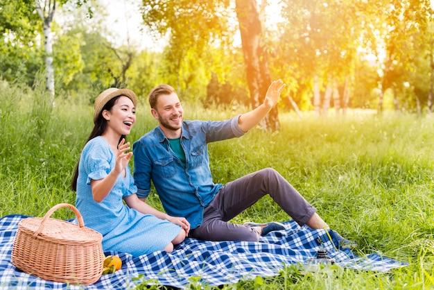 Joven pareja feliz saludando y sonriendo en picnic en la naturaleza