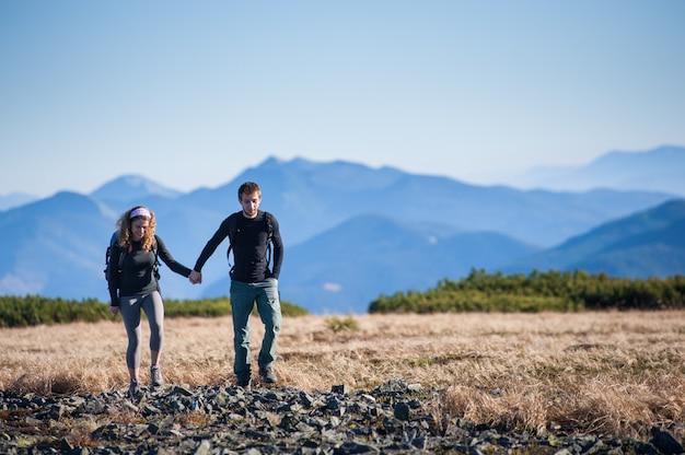 Joven pareja feliz senderismo en las hermosas montañas