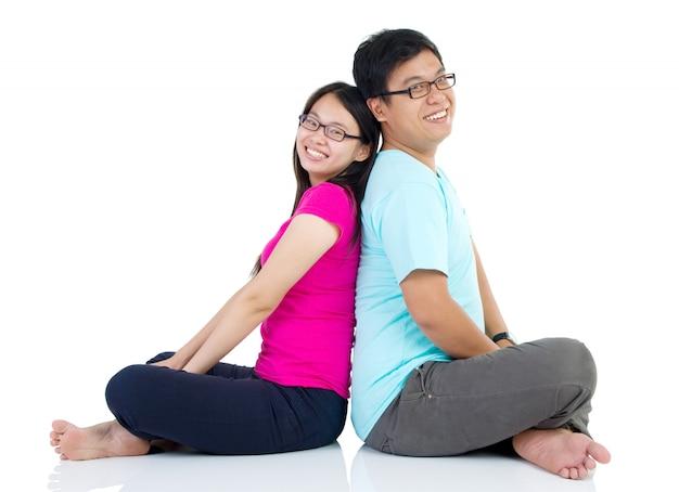 Joven pareja feliz sentados juntos