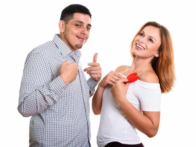 Joven pareja feliz sonriendo y enamorado de mujer sosteniendo corazón rojo en el pecho y pensando