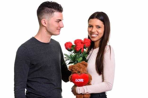 Joven pareja feliz sonriendo y enamorado de mujer sosteniendo ramo de rosas rojas