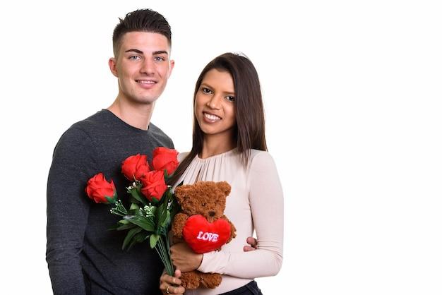 Joven pareja feliz sonriendo mientras sostiene rosas rojas y osito de peluche