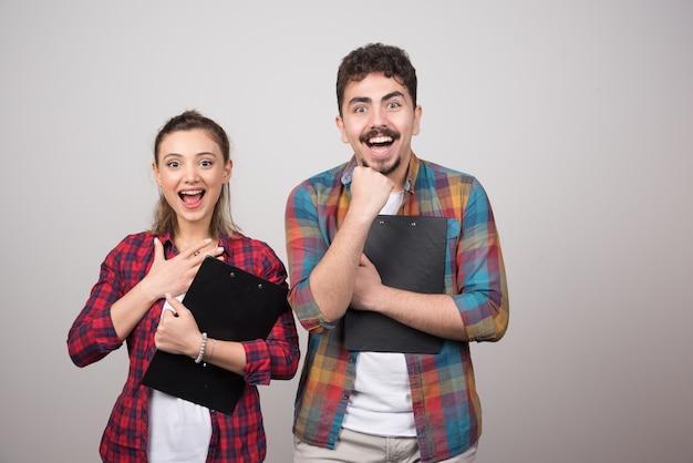 Joven pareja feliz sosteniendo portapapeles y sonriendo