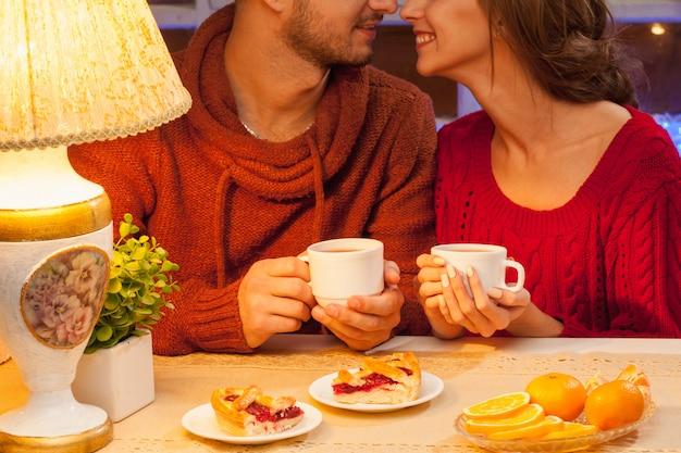 La joven pareja feliz con tazas de té y pasteles.