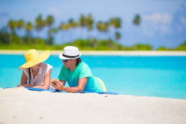 Joven pareja feliz con teléfono móvil en la playa