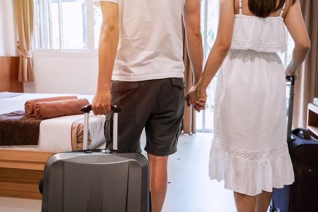Joven pareja feliz viajero con equipaje en la habitación del hotel en vacaciones de verano