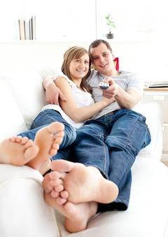Joven pareja feliz viendo la televisión acostado en el sofá