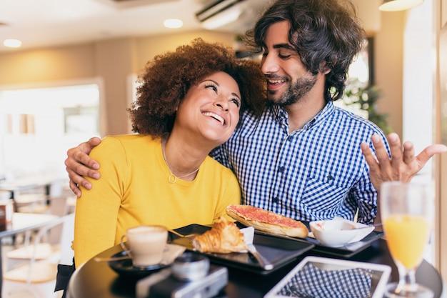 Joven pareja fresca desayunando en la cafetería. ellos están bebiendo jugo de naranja y comiendo una