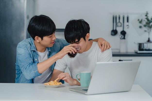 Joven pareja gay alimentación comida y merienda usando la computadora portátil en casa moderna. los hombres lgbtq asiáticos felices se relajan y se divierten usando las redes sociales de tecnología juntos mientras se sientan en la cocina de la casa.