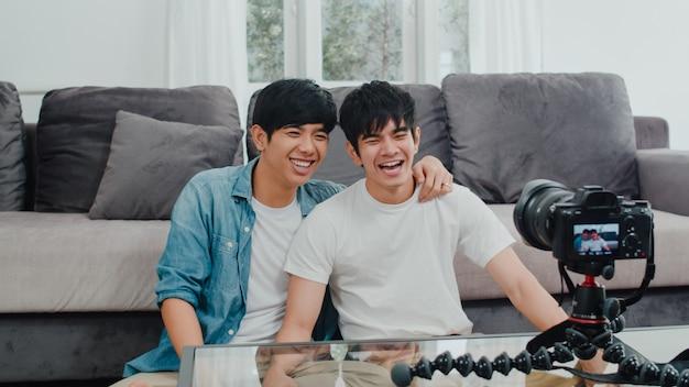 Joven pareja gay asiática influyente pareja vlog en casa. adolescentes coreanos lgbtq hombres felices relajarse diversión usando cámara grabar vlog video subir en las redes sociales mientras está acostado sofá en la sala de estar en casa.