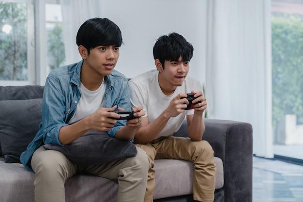 Joven pareja gay asiática juega juegos en casa, hombres adolescentes coreanos lgbtq usando joystick que tienen divertido momento feliz juntos en el sofá en la sala de estar en casa.