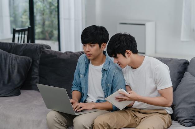 Joven pareja gay asiática trabajando portátil en casa moderna. asia lgbtq + hombres felices relajarse divertirse usando la computadora y analizar sus finanzas en internet juntos mientras se está acostado en el sofá de la sala de estar en casa.