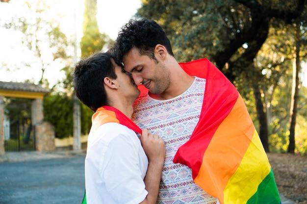 Joven pareja gay enamorada envuelta en la bandera del orgullo feliz pareja lgbt en una cita hombres enamorados