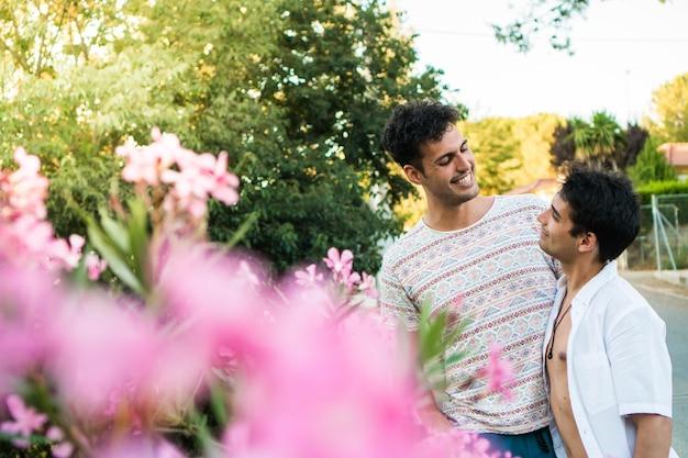 Joven pareja gay enamorada en la naturaleza dos jóvenes gays al aire libre en verano feliz pareja lgbt