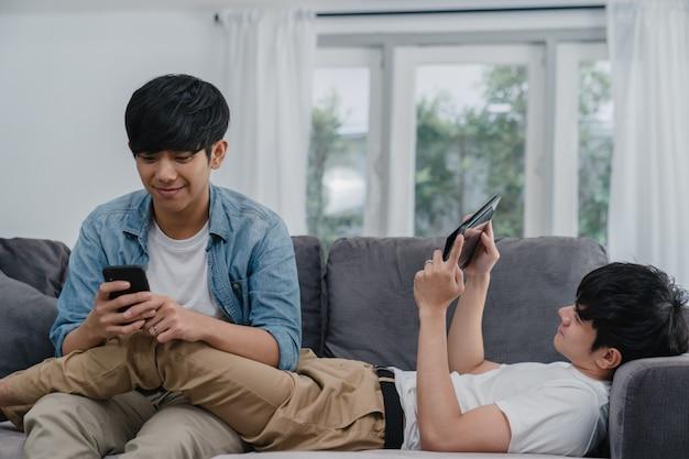 Joven pareja gay lgbtq utilizando teléfono móvil y tableta en casa moderna. hombre asiático amante feliz relajarse risa y diversión tecnología jugar juegos en internet juntos mientras está acostado sofá en la sala de estar.