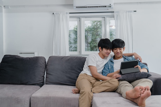 Joven pareja gay con tableta en casa. los hombres asiáticos lgbtq + felices se divierten y se divierten usando la tecnología para ver películas en internet juntos mientras descansan en el sofá de la sala.