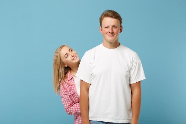 Joven pareja hermosa alegre dos amigos hombre y mujer en camisetas en blanco vacío rosa blanco posando
