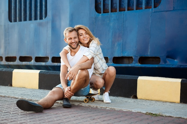 Joven pareja hermosa caminando por la ciudad, sonriendo, sentado en patines.